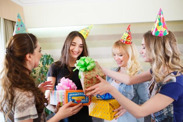 美しい少女は彼のガールフレンドの誕生日に贈り物をします。 Premium写真