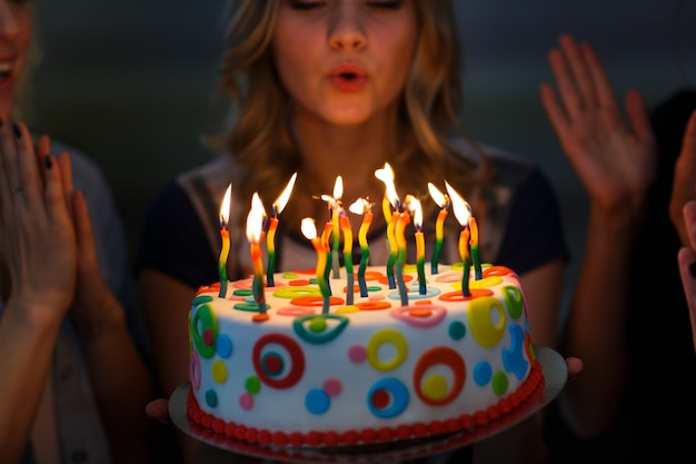お誕生日。キャンドルケーキの女の子。 Premium写真