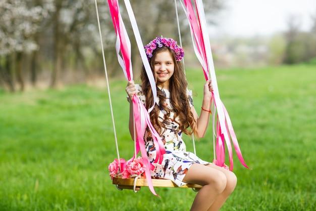 ブランコに乗っている少女、公園で少女、かわいい女の子、少女 Premium写真