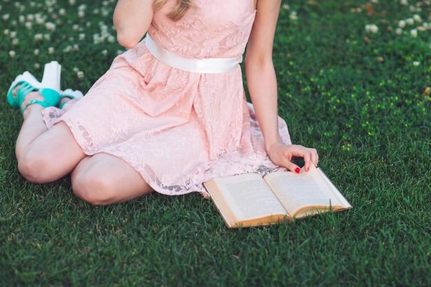 Маленькая девочка сидя на траве и читая книгу. Premium Фотографии