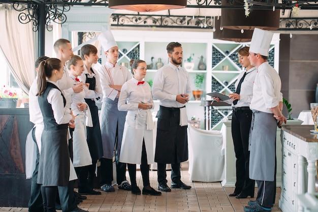 Менеджер ресторана и его сотрудники на террасе, общаясь с шеф-поваром в ресторане, Premium Фотографии