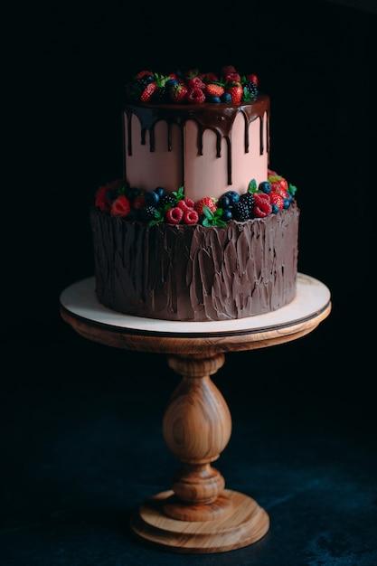 黒の木製スタンドにフルーツチョコレートケーキ Premium写真