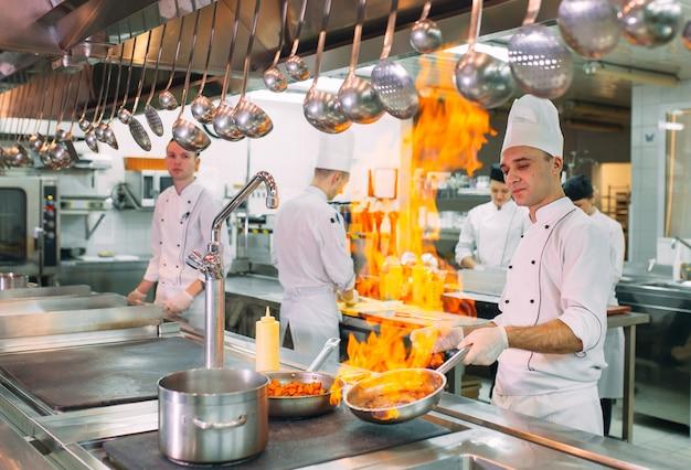 料理人はレストランやホテルのキッチンのコンロで食事を用意します。 Premium写真