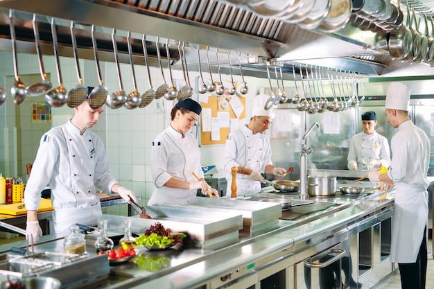 Повара готовят еду на кухне ресторана. Premium Фотографии