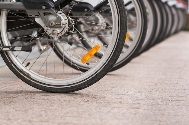 歩道にレンタル用の駐輪ビンテージ自転車バイクの行。 Premium写真