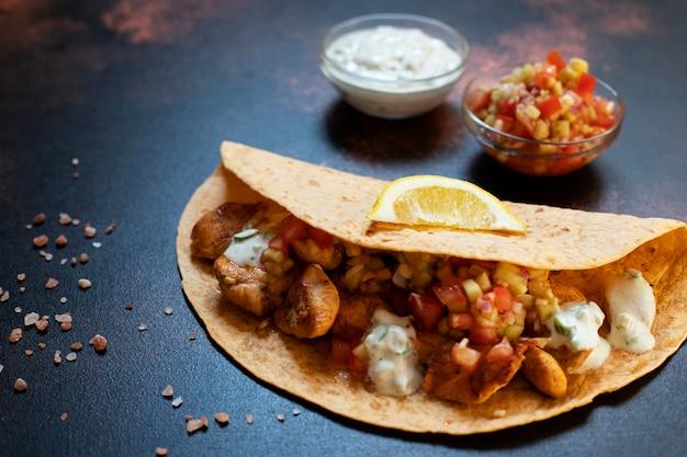 チキンと野菜の伝統的なメキシコのファヒータ。トルティーヤに白と赤のソース、レモン、新鮮なねぎを添えて。閉じる。暗い背景。コピースペース Premium写真