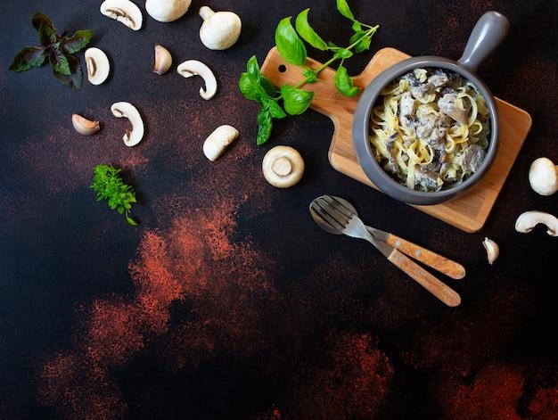 キノコとクリームソースの自家製イタリアンフェットチーネパスタとバジル(フェットチーネアルフンギポルチーニ)のグレーのフライパンで提供しています。イタリア料理。暗い素朴な背景、上面図、コピースペース Premium写真