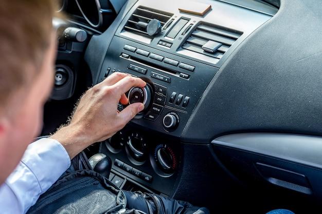 Человек едет за рулем, ищет хорошую музыку Premium Фотографии