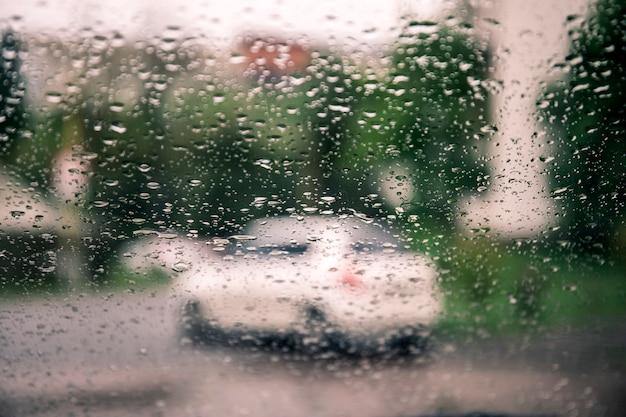 都市と車のライトの景色を背景をぼかした写真に対して車のガラスに雨滴。 Premium写真