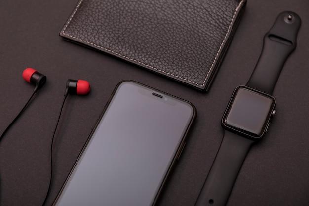 黒革の財布、スマートウォッチ、スマートフォン、イヤホンのセット。 Premium写真