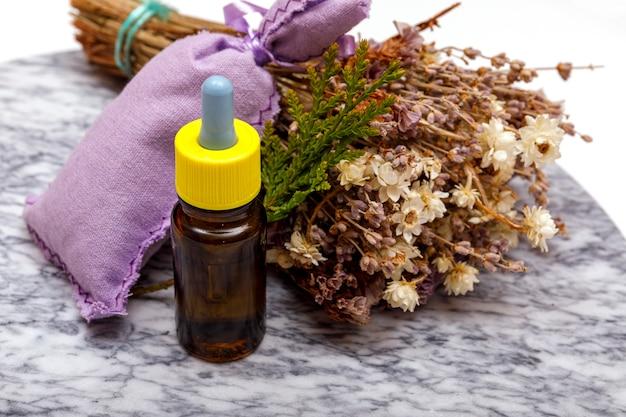 Эфирное масло и цветки лаванды. выбор эфирного масла на мраморном столе с различными органическими травами и цветами Premium Фотографии