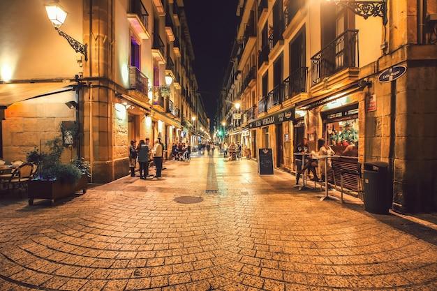 夜の活気のあるタパスバーやレストランのあるサンセバスチャンの典型的な小さなストリートビュー Premium写真