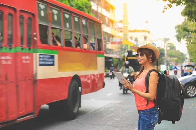 黒のバックパックと帽子バンコクでタブレットの地図を見て若い女性旅行者。旅行のコンセプト Premium写真