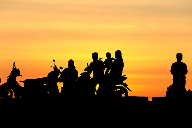 シルエットの人々と日没、シルエット写真でバイクに家族 Premium写真