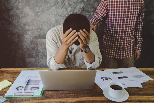 Человек подбадривал своего депрессивного друга, старался из-за работы. бизнес-проблема, финансовая и инвестиционная концепция Premium Фотографии