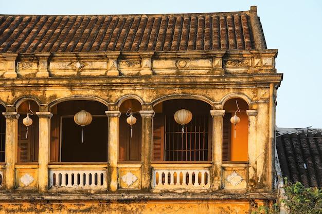 Старые дома в хое древний город с фонарями, висящими на окне Premium Фотографии