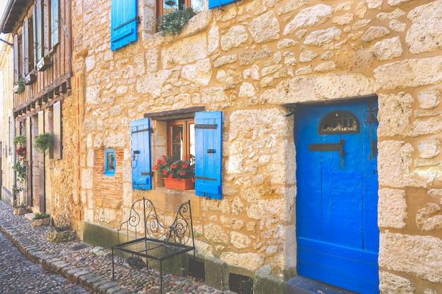 フランス、ベルジュラックの町の木製のドアと青い窓の石造りの家のファサード Premium写真