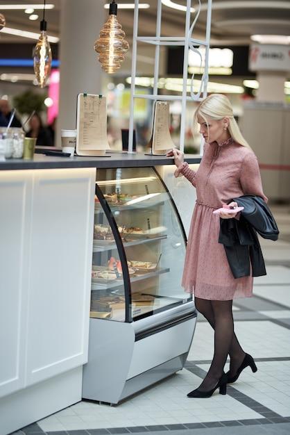 ショッピングセンターのカフェで携帯電話を持ち、紙コップを手に持った若い女性。 Premium写真