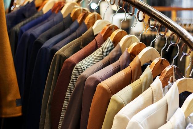 店のハンガーにスタイリッシュなメンズジャケット、クローズアップ Premium写真