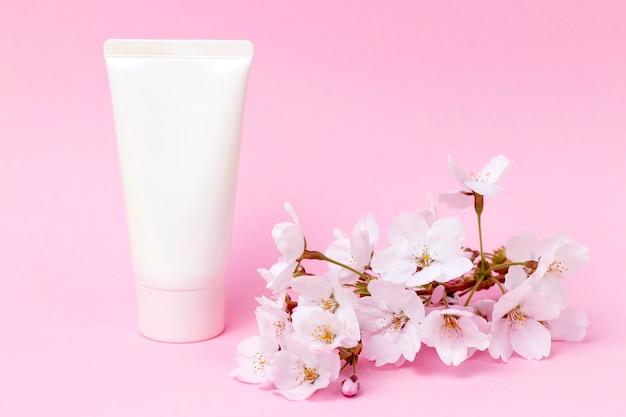 ピンクの背景、正面、化粧品ケアの概念上のクリームとチューブ Premium写真