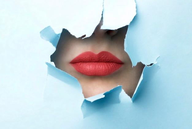 赤い唇と青い引き裂かれた紙の背景 Premium写真