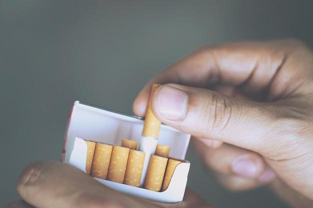 男の手持ち株を閉じるそれをタバコのパックからはがすそれはタバコを吸う準備をします。 Premium写真