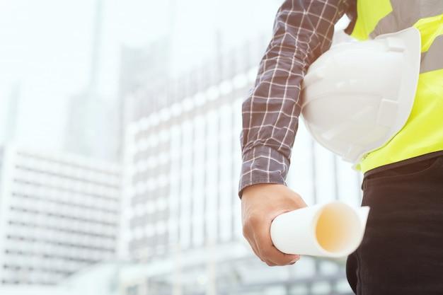 ロール紙を保持しているエンジニアリング男性建設労働者のクローズアップ Premium写真