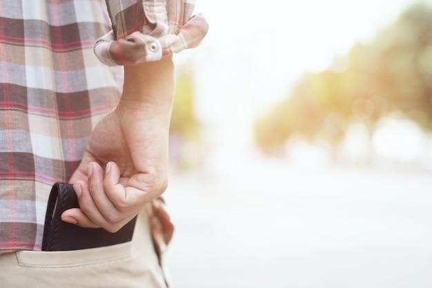 あなたの財布を彼の後ろポケットの後ろポケットに安全に保つことでポーズをとって自信を持っているビジネスマン。 Premium写真