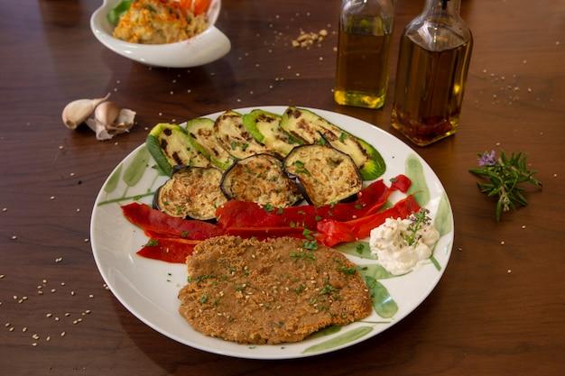Пирог из сухофруктов сейтан с овощами гриль. здоровая веганская еда Premium Фотографии