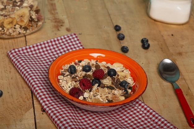 オート麦フレーク、ナッツ、ブルーベリー、ラズベリーのヘルシーな朝食 Premium写真