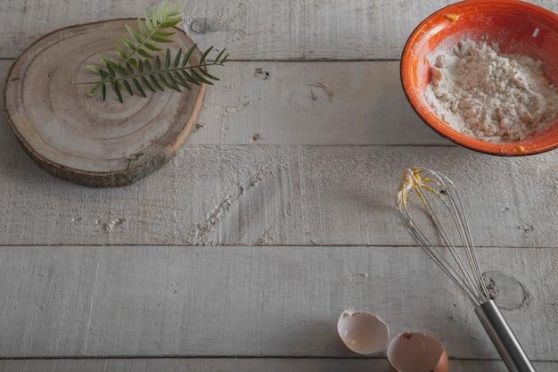Ингредиенты и инструменты, чтобы сделать тесто, муку, яйца и венчик на белом деревянном дне. Premium Фотографии