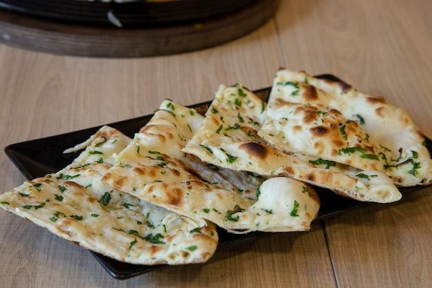 木製のテーブルにガーリックバターとインドのナンパン Premium写真