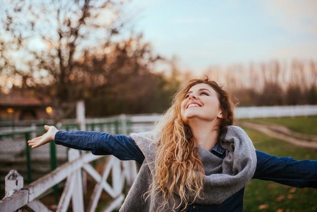 Свободу чувствую хорошо. радостная женщина поднимая руки снаружи. Premium Фотографии