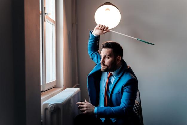 ハエたたきでハエを打ちます。ビジネスの男性がハエを追いかけています。 Premium写真