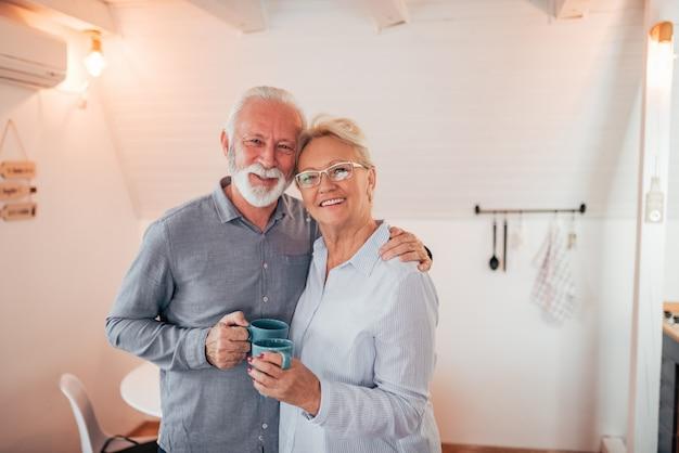 Домашний портрет старшей пары держа кружки, смотря камеру. Premium Фотографии