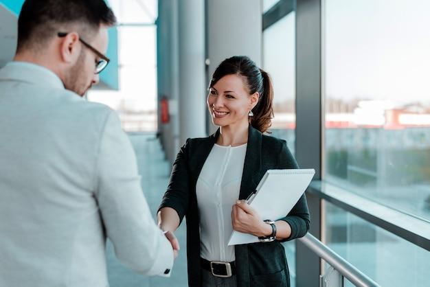 Два улыбающихся деловых людей рукопожатие. хорошая коммерческая сделка. Premium Фотографии