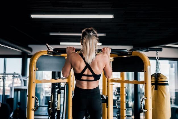 筋肉の若い女性がジムで運動をします。 Premium写真
