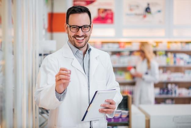 Портрет красивый фармацевт с буфером обмена, улыбка на камеру. Premium Фотографии