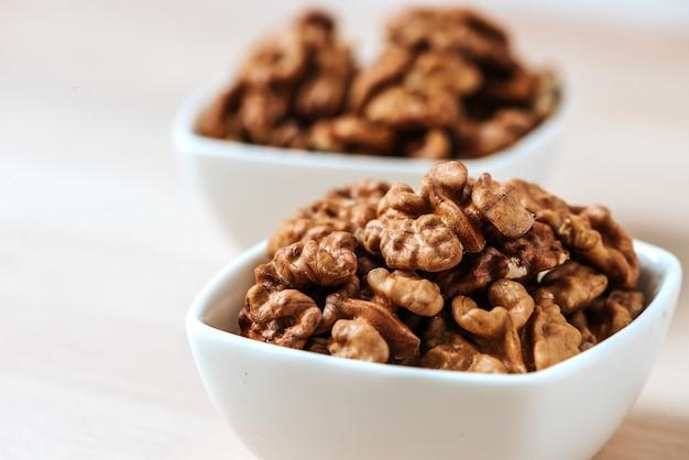 Грецкие орехи в двух белых чашах. крупный план. Premium Фотографии