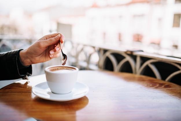 Женская рука держит ложку возле чашки кофе на открытом воздухе. Premium Фотографии