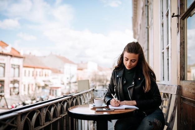 若い女性が街のテラスに座りながら日記を書く。 Premium写真