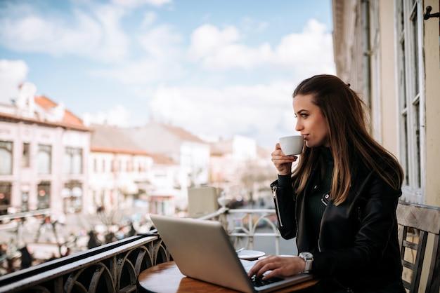 ラップトップに取り組んでテラスでコーヒーを飲む女性。 Premium写真