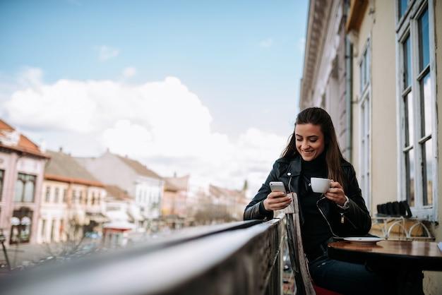 一杯のコーヒーを楽しんで、旧市街の中心部のバルコニーで電話を使用して。 Premium写真