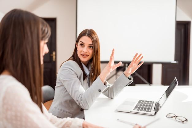 Элегантная коммерсантка говоря к ее работнику или клиенту на конференц-зале. Premium Фотографии