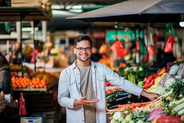Молодой продавец человек на фермерском рынке. Premium Фотографии