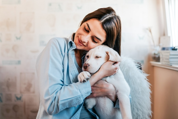 Красивая девушка брюнет обнимая ее щенка дома. крупный план. Premium Фотографии