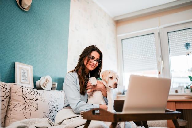 Девушка с щенком, имея видео звонок на ноутбуке. Premium Фотографии