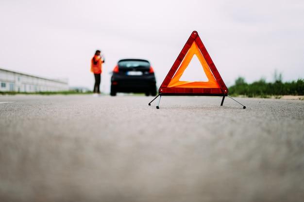 道路上の前景に赤い警告もつれ。バックグラウンドで反射ベストの女の子。 Premium写真