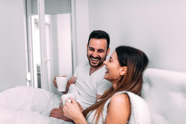 コーヒーを飲みながら笑ってベッドでカップル。 Premium写真