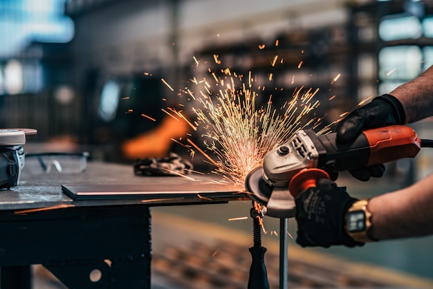 小型グラインダーで金属を挽くクローズアップ。 Premium写真